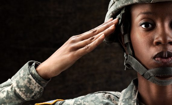 female African American in army camouflage uniform and combat helmet.